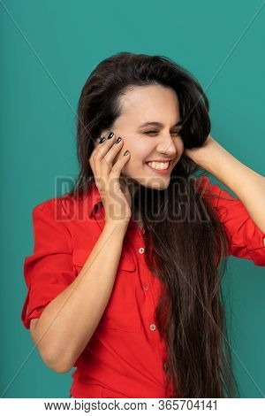 Laughing Woman With Closed Eyes Touches Face With Hands, Pretty Brunette Woman In Red Casual Blouse