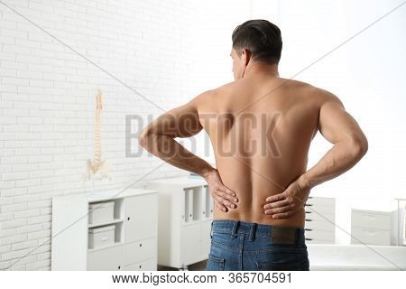 Man Suffering From Lower Back Pain At Clinic. Visiting Orthopedist