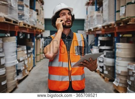 Tensed Warehouse Manager Holding Digital Tablet While Talking On Mobile Phone Looking Stressed