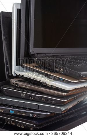Stack Of Used Laptops In Different Colors And Models. T