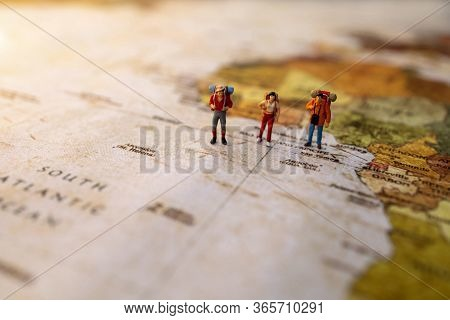 Minature People: Traveling With A Backpack Standing On Vintage World Map, Travel And Vacation Concep