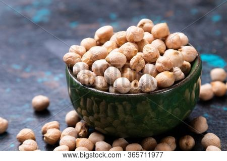Dry chickpeas or garbanzo beans in ceramic bowl, healthy food ingredient
