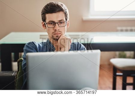 Focused Young Businessman In Eyewear Looking At Laptop At Home, Disappointed With Bad News, Feeling