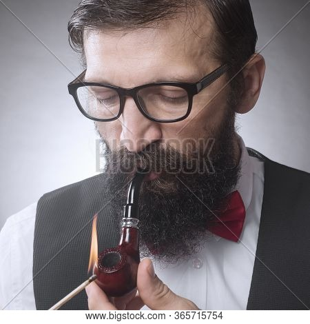The Bearded Man With Eyeglasses Is Igniting And Smoking Tobacco Pipe.