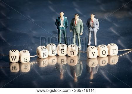 Miniature Model Of Businessmen And Wooden Cubes With We Need You Inscription Strung On A Thread On R