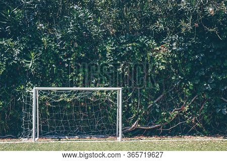 Soccer Goal At The Outdoor Amateur Field Surrounded By Green Plant Wall. Close To Nature, Healthy Sp