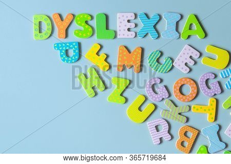Word Dyslexia Written Of Wooden Letters And Scattered Letters Below On Azure Background. Inscription