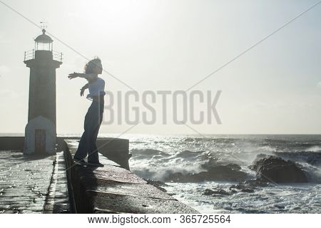 Multicultural woman walks along the railing of ocean promenade near the lighthouse in the fog with a foaming surf.