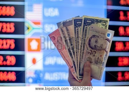 Hands Holding Multiple Currency Notes Like American Dollar, Malaysian Ringgit, Singapore Dollar, Ind