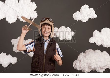 a boy plays with a cardboard airplane and dreams of becoming a pilot, dressed in a retro style jacket and helmet with glasses, clouds of cotton wool, gray background, tinted in brown