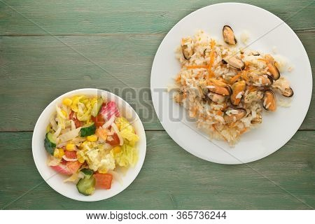 Rice With Mussels And Carrots On A White Plate. Rice With Mussels And Carrots On A Green Wooden Back