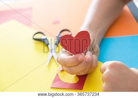 Paper Crafts For Kids. Child Hands Cuts Colored Paper With Scissors And Holding Red Paper Heart