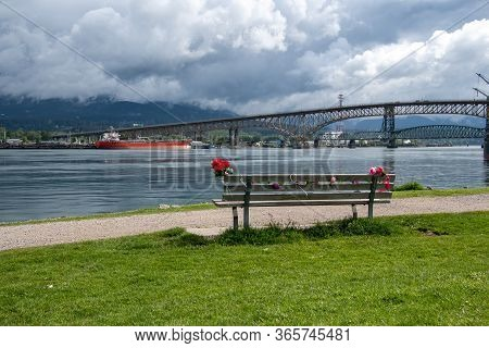 A Bench Decorated With Flowers, And The Second Narrows Bridge In The Background.  Vancouver  Bc  Can