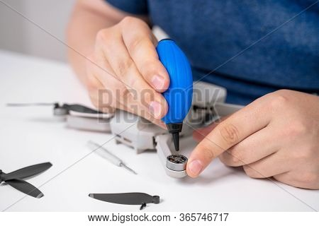 The Human Hands Making Maintenance With Drone Device, Using Blue Rubber Air Pump Cleaner Or Silicone