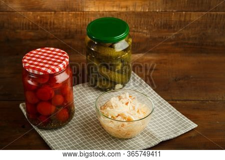 Jars Of Pickled Tomatoes And Cucumbers With Homemade Pickles And Sauerkraut On A Wooden Table.
