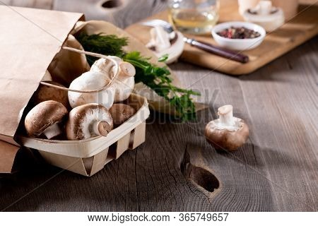 Delivery Of Products. Champignon Mushrooms And Fresh Greens In Eco-friendly Packaging On A Wooden Ta