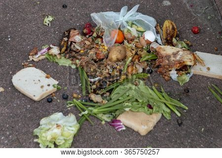 A Close Up View Of A Food Recycling Bucket That Has Fallen Over And The Contents Has Fallen Out Onto