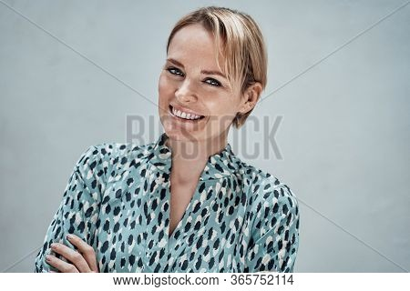 Cheerful And Attractive Adult Woman With Short Blonde Hair Posing Over The Grey Background, Wearing