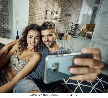 Beautiful young loving couple making selfie at home, smiling happy.