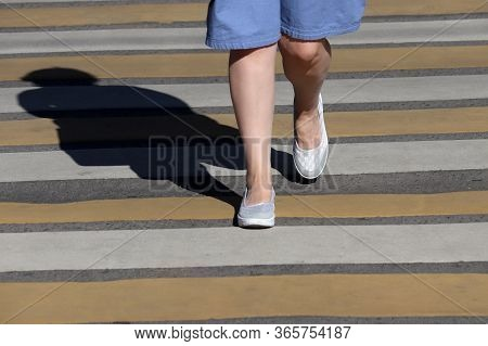 Female Legs On Pedestrian Crossing, Street Safety Concept. Woman In A Summer Dress Walking On On The