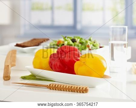 Healthy, low calorie food on tabletop, plate of sweet peppers, salad and brown bread.