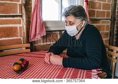 Elderly Woman, Grandma Wearing A Mask Sitting Inside The House By The Window Alone, Looking Sad And