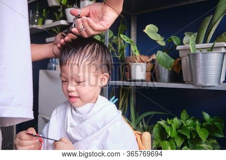 Cute Smiling Asian Young Boy Getting A Haircut At Home, Father Makes A Haircut For His Son With Scis