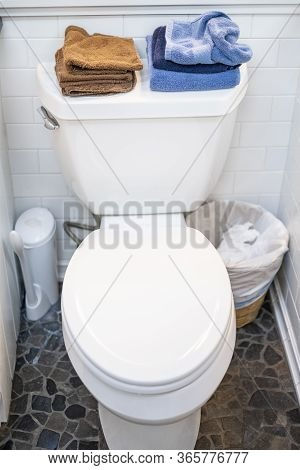 Clean Toilet With Closed Lid, With Towels And Cloths On Top.