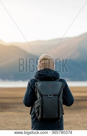 Hipster Man Traveler With Sweater And Backpack Traveling At Napa Lake, Happy Young Hiker Looking Mou