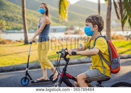 Active School Kid Boy And His Mom In Medical Mask Riding A Bike With Backpack On Sunny Day. Happy Ch