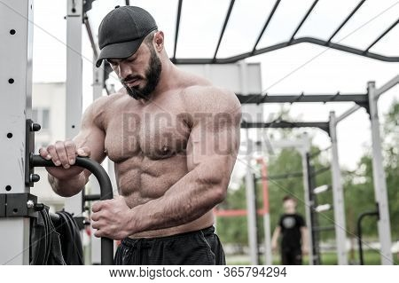 Young Bearded Man In Cap With Perfect Body Physique On Street Outdoor Gym Trainer During Fitness Tra