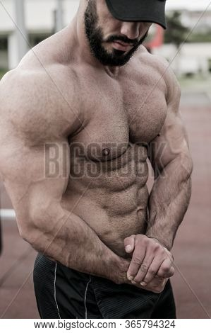 Strong Young Caucasian Man With Beard Showing Perfect Muscle Physique Development During Outdoor Wor