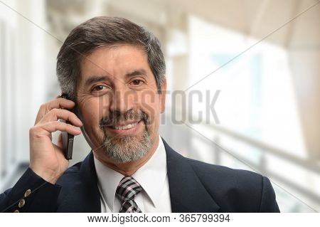 Mature hispanic businessman on the cell phone inside an office building