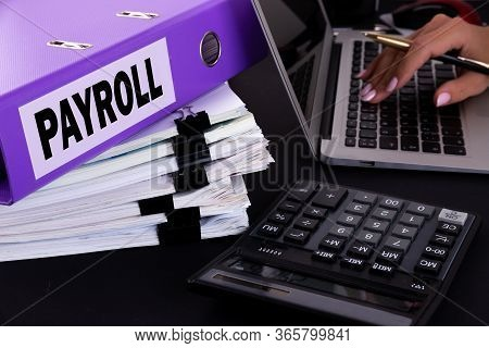 Text, Word Payroll Is Written On A Folder Lying On Documents On An Office Desk With A Laptop And A C