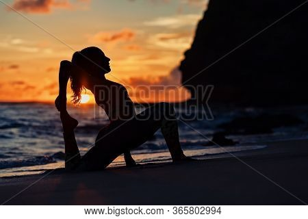 On Sunset Sea Beach Sporty Young Woman Doing Exercise, Stretching To Keep Feet. Healthy Lifestyle Da