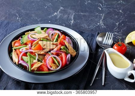Quick Lunch: Green Bean, Cucumber And Canned Tuna Salad With Tomatoes And Red Onion On A Black Plate