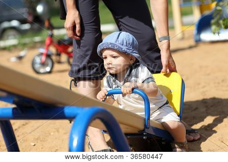 Child Sitting On Seesaw