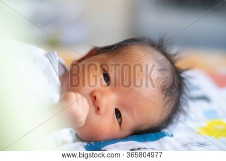 Innocence Adorable Cute Newborn Baby Infant With Big Black Eyes Lying On The Bed