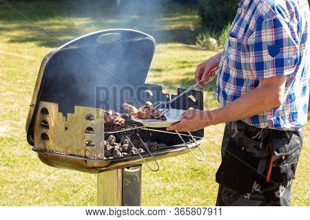A Man At The Charcoal Grill Is Grilling Steaks, Grill Sausages And Chicken Wings And Using Barbecue