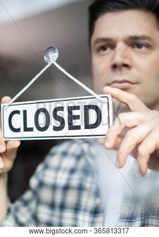 Male Small Business Owner With Serious Expression Putting Up Closed Sign During Recession Or Health