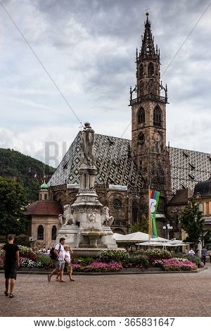 Bolzano, Italy - August 13, 2019: People Walking Past Bolzano Cathedral On A Cloudy Day