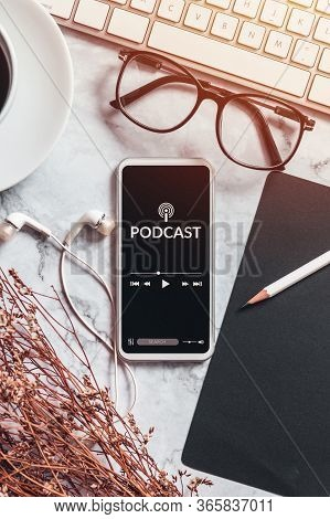 Podcast Audio Content Concept. Podcast Application On Mobile Smartphone Screen On Workspace Desk Wit