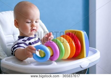 Baby Game. Little Clever Caucasian Child Playing Colorful Plastic Toys Pyramid Sitting On Highchair.