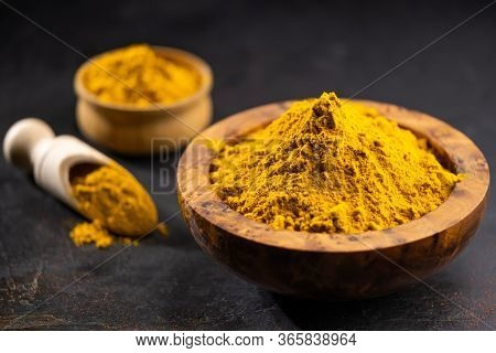 Turmeric powder or curcuma powder in a wooden bowl on a dark background, close-up. Cooking ingredients, flavor.
