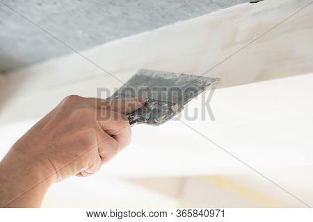 Worker putsty plasterboard ceiling in new appartment. Repairman works with plasterboard, plastering dry-stone wall, home improvement. A man makes repairs at house. Putty knife in male hand. Hand work