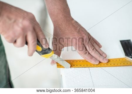 Styrofoam, seiling mounting. A man cuts foam. Warming. Repair in the house. DIY repair. Work with polystyrene foam, insulation of walls and ceiling. Male hands with tools closeup