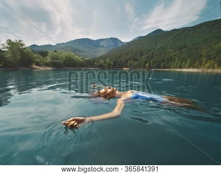 Freedom Carefree Woman In Blue Swimwear Relaxing, Swimming And Enjoying Fresh Colored Water In Mount