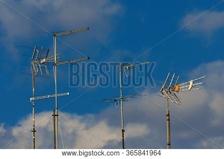Different Kinds Of Tv Antennas And Arrays With Blue Sky And Clouds