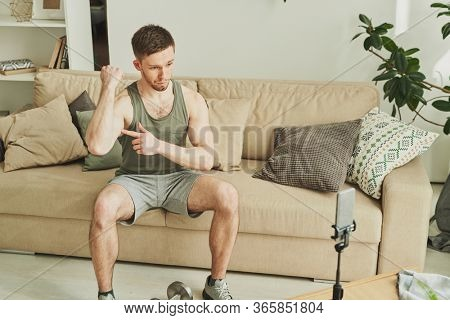 Young athlete boasting with his power in front of smartphone camera during live stream of home training while pointing at his bicep