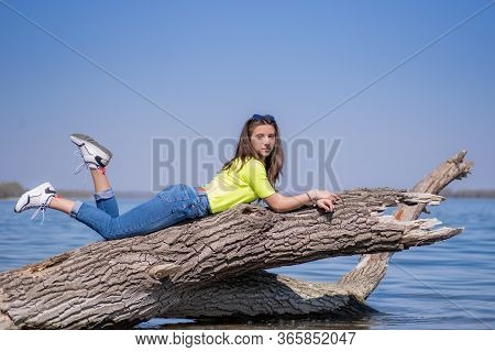 Young Attractive Girl With Brown Long Hair, Sitting On A Log Above The River, Enjoying The Sun Warml